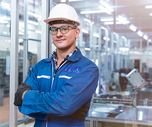 Industrial worker in a hard hat standing in a modern factory